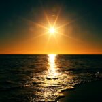 image of sun setting over water